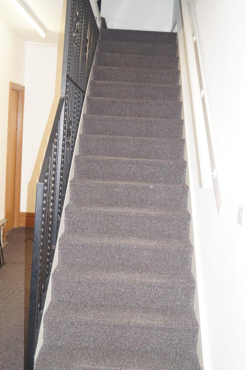 Staircase leading to shared kitchen